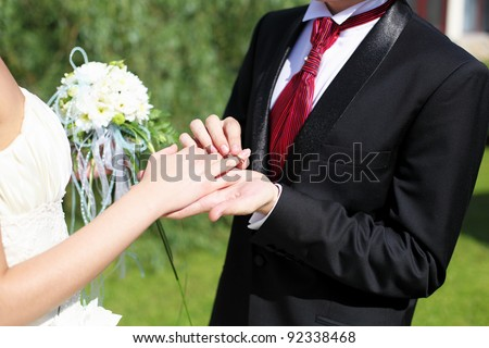 Shot moment when the groom puts the ring on a young bride's hand. - stock photo