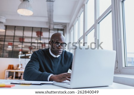 Shot of a bald african businessman working on laptop computer in office. Young web designer sitting at his desk working. - stock photo