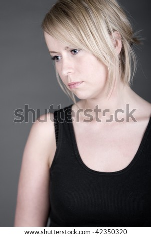 Shot of a Beautiful but Sad Looking Blonde Woman against Grey Background - stock photo