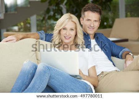 Shot of a beautiful couple relaxing at home on the sofa. Smiling blonde woman using laptop while sitting next to handsome man an searching for travel destination.
