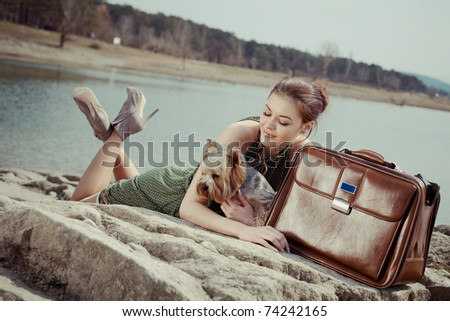 Shot of a beautiful girl on the lake with a suitcase and a dog (Yorkshire terrier) - stock photo