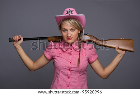 Shot of a beautiful glamour young girl with shotgun over her back - stock photo