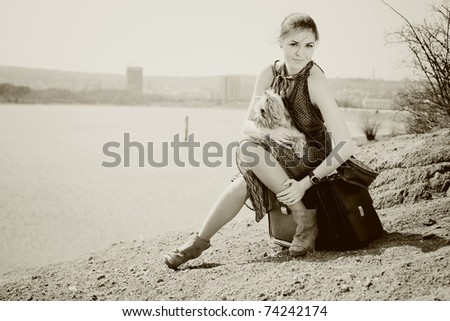 Shot of a beautiful woman sitting on suitcase on the banks of the lake with the dog (Yorkshire terrier). In Black & White - stock photo