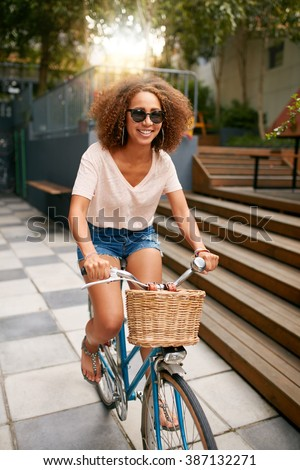 Shot of a beautiful young woman riding her bike on sidewalk. African young girl wearing sunglasses enjoying bicycle ride. - stock photo