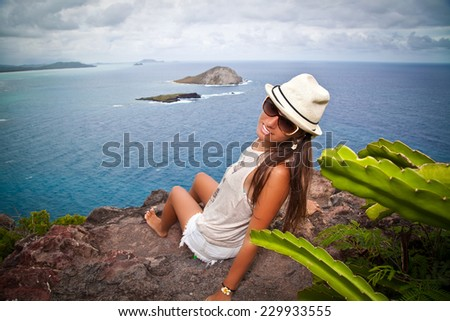 Shot of a beautiful young woman smiling while taking a break from hiking through the mountains. Adventurous and carefree. View of the Windward side of O'ahu.