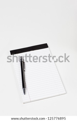 Shot of a black metal ball point pen resting on a white legal letter pad.