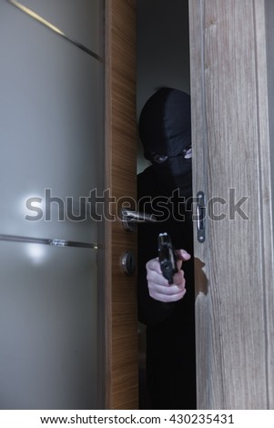 Shot of a burglar holding a gun and sneaking into a room