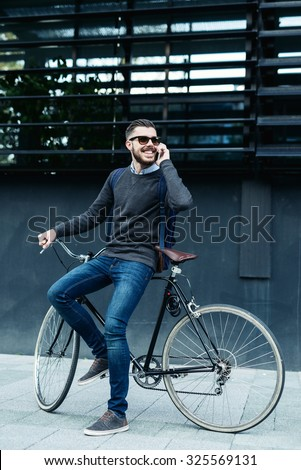 Shot of a businessman using his cellphone while going to work with his bicycle. Selective focus, narrow depth of field. - stock photo