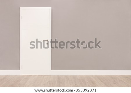 Shot of a closed white door on a gray wall in an empty room - stock photo