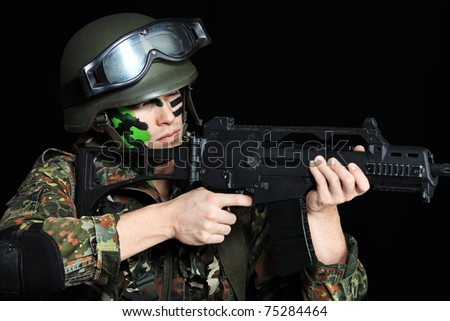 Shot of a conceptual soldier painted in khaki colors. Over black background.