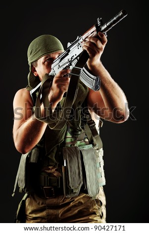 Shot of a conceptual soldier painted in khaki colors. Over black background. - stock photo
