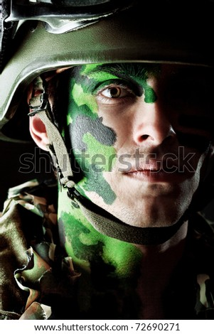 Shot of a conceptual soldier painted in khaki colors. Studio shot over black background. - stock photo