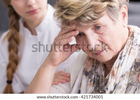 Shot of a concerned senior woman and a nurse sitting behind her and holding her arm - stock photo
