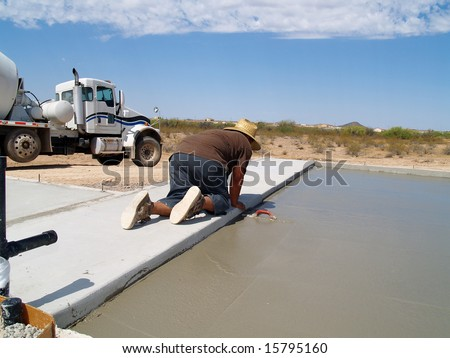 Shot of a construction worker smoothing out a freshly poured concrete slab using a hand trowel. Horizontally framed shot. - stock photo