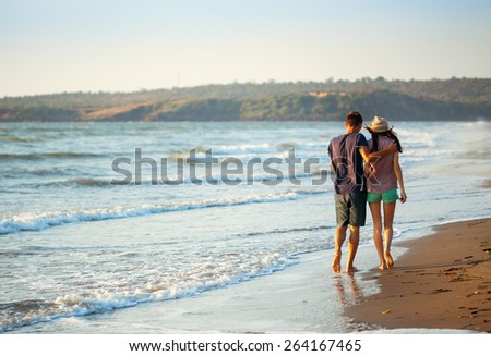 Shot of a couple enjoying a romantic evening on the beach at sunset - stock photo