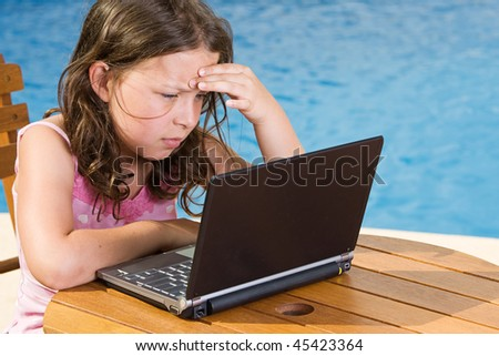 Shot of a Cute Child Using her Laptop by the Pool - stock photo