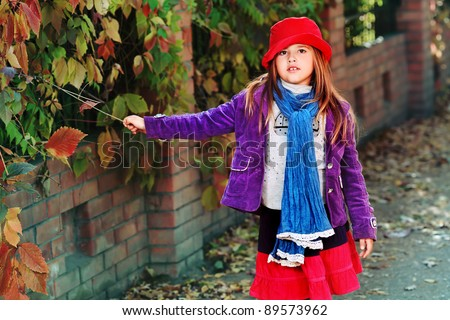 Shot of a cute girl at the autumn park. Retro style.