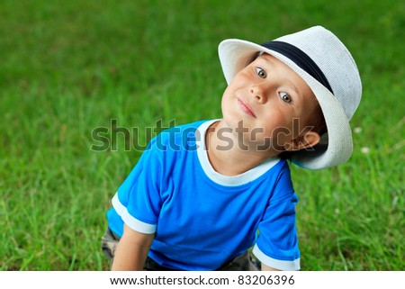 Shot of a cute little boy in a hat outdoor. - stock photo