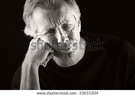 Shot of a Depressed Senior Man against a Dark Background - stock photo