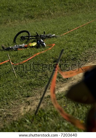 Shot of a downhill rider laying on the grass. Accident.