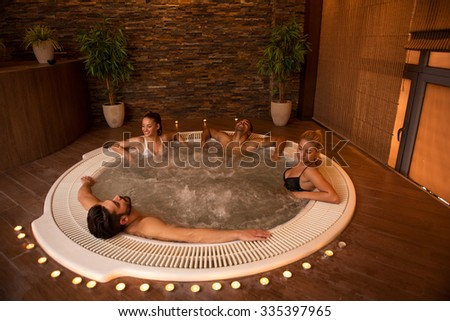 Shot of a friends enjoying in a jacuzzi. Higher ISO values, natural light. - stock photo