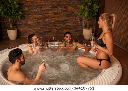 Shot of a friends enjoying in jacuzzi and drinking white wine. - stock photo