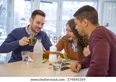 Shot of a friends having a great time in cafe.Friends smiling and sitting in a cafe, drinking tea and enjoying together. - stock photo