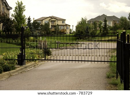 Shot of a gated community of million dollar homes, at the entrance, showing security items such as lights, key card pad and security camera.