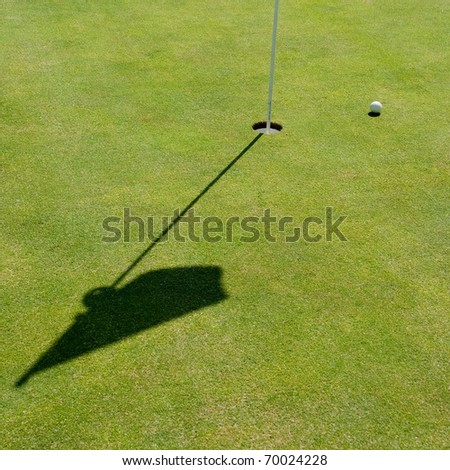 Shot of a golf hole with a flag and a ball close by