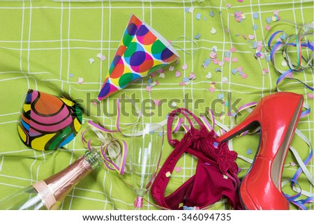 Shot of a green tablecloth after a party celebration with confetti, empty bottle, glass of champagne with lipstick imprint, party popper, red court shoe and rd panties. - stock photo