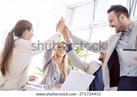 Shot of a group of colleagues high-fiving each other during an informal meeting - stock photo