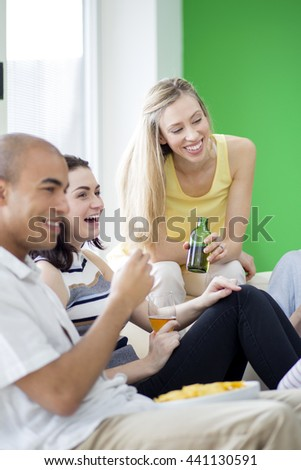 Shot of a group of friends eating and drinking at home. - stock photo