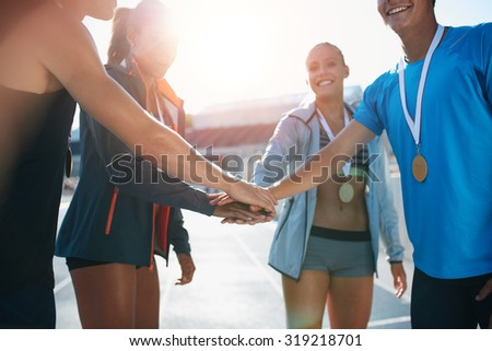 Shot of a group of young sportsmen with medals piling their hands while standing in a huddle. Successful team of athletes with their hands together cheering victory. - stock photo