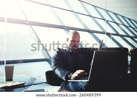 Shot of a handsome businessman typing on computer keyboard and reviewing documents sitting in light modern office interior, managing director examining paperwork in coffee shop, flare sun light - stock photo