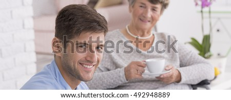 Shot of a handsome caregiver sitting close the smiled senior woman
