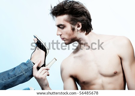 Shot of a handsome man holding woman's leg in elegant shoes. - stock photo