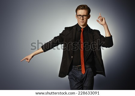 shot of a handsome young man in elegant black suit posing with expression. Studio shot. - stock photo