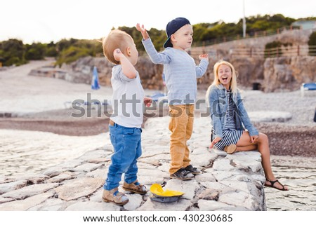 Shot of a happy family of three enjoying game on the shore. Family love makes the world brighter