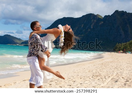 Shot of a happy young couple enjoying a romantic day on the beach. Couple having fun on romantic travel honeymoon vacation, summer holidays romance. Young happy lovers.