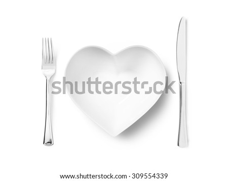 Shot of a heart shaped plate or bowl with a silver knife and fork implying a love of healthy eating. The image has copy space and a clipping path for each of the items.  - stock photo