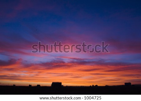 Shot of a landscape with a beautifull red, blue and orange toned sky. - stock photo
