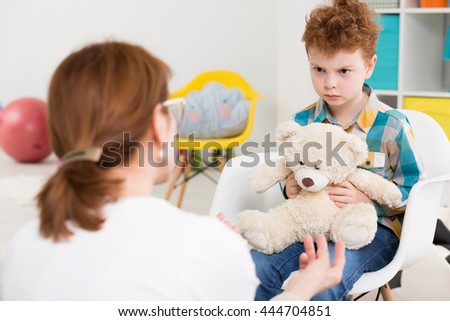 Shot of a little angry boy holding his teddy bear during a therapy session with his psychologist