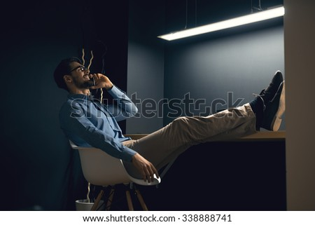 Shot of a man relaxing and talking on mobile phone. - stock photo