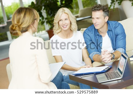 Shot of a middle aged happy couple planning their future while consulting with insurance agent in their home.