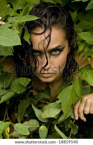 Shot of a model's face with heavy eye makeup surrounded by green leaves - stock photo