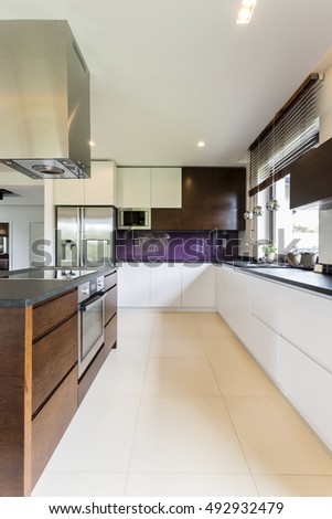 Shot of a modern spacious kitchen with white and brown furniture