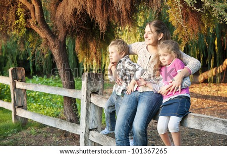 Shot of a mother and her two children in a beautiful garden in autumn - stock photo