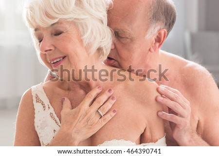 Shot of a naked senior man passionately kissing his wife on the neck