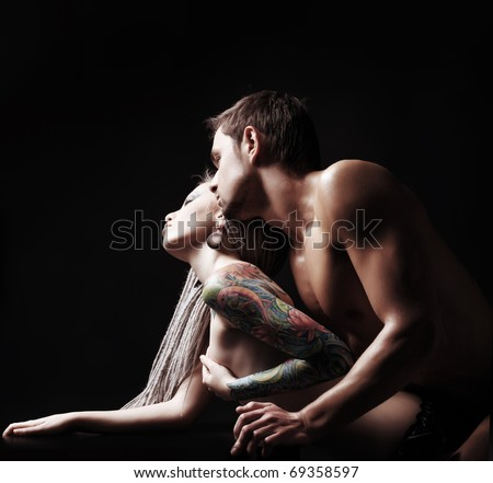 Shot of a passionate loving couple. Over black background. - stock photo