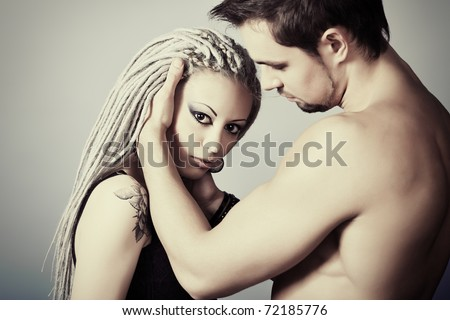 Shot of a passionate loving couple. Over grey background.